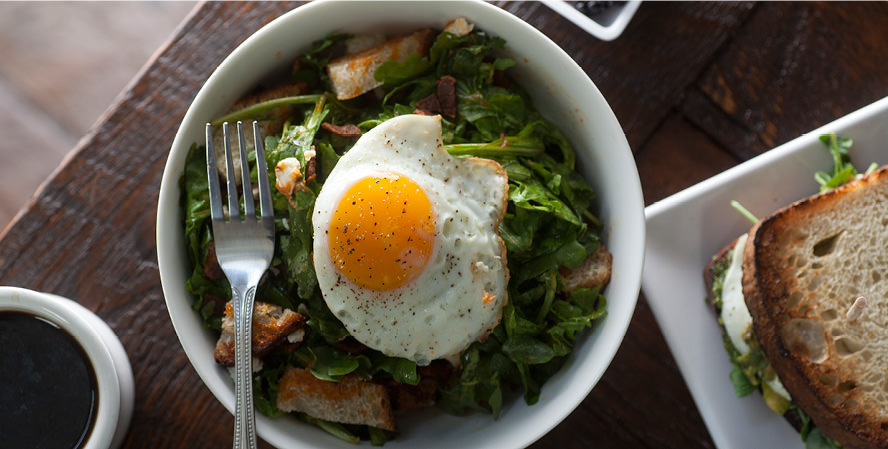 feed_cafe_1_fried_egg_on_top_of_greens_in_a_bowl