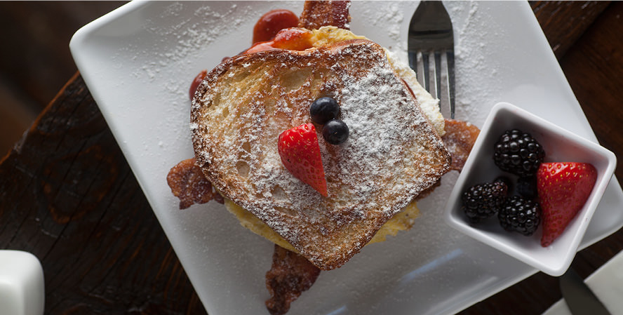 feed_cafe_3_french_toast_breakfast_sandwich_with_bacon_and_eggs_with_a_side_of_fresh_fruit